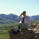 Businessman on the phone in front of a laptop outdoors.